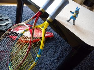 two tennis rackets leaning on a bench