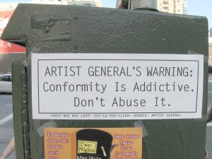 Sign in urban landscape saying Conformity is Addictive; don't abuse it.