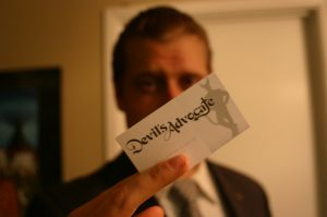 Man holding business card that says Devil's Advocate