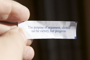 A fortune from a fortune cookie that says the purpose of argument is not victory but progress