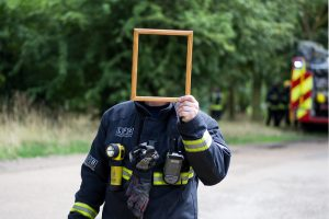 Man holding up mirror in front of face so his identity is obscured